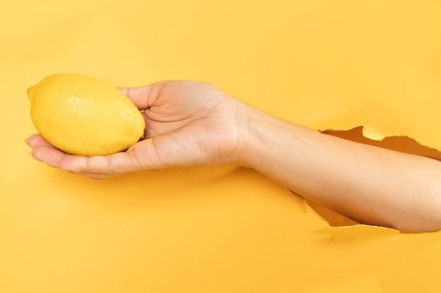Close-up hand holding organic lemon