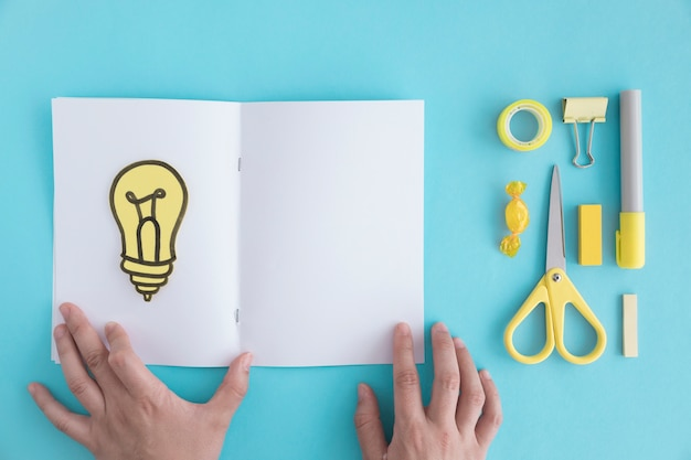 Close-up of hand holding page with light bulb and stationery on blue background