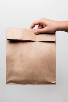 Close-up hand holding paper bag