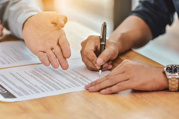 Close up hand holding pen sign contract on document