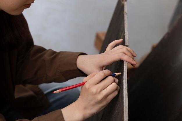 Chiuda sulla matita della holding della mano