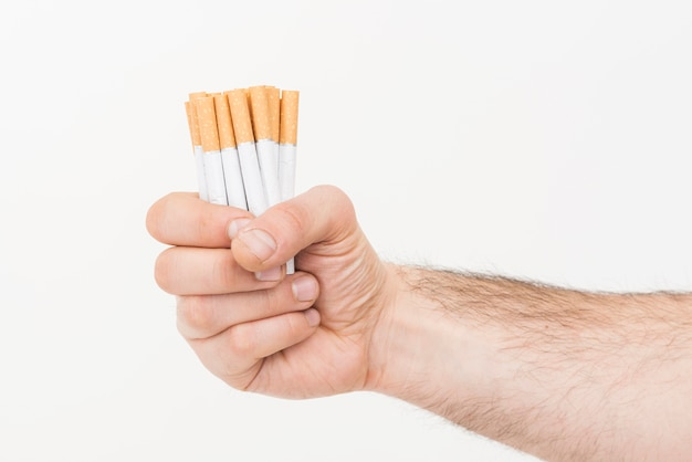 Close-up of hand holding pile of cigarettes against white background
