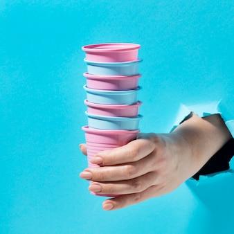Primo piano mano che tiene mucchio di bicchieri di plastica