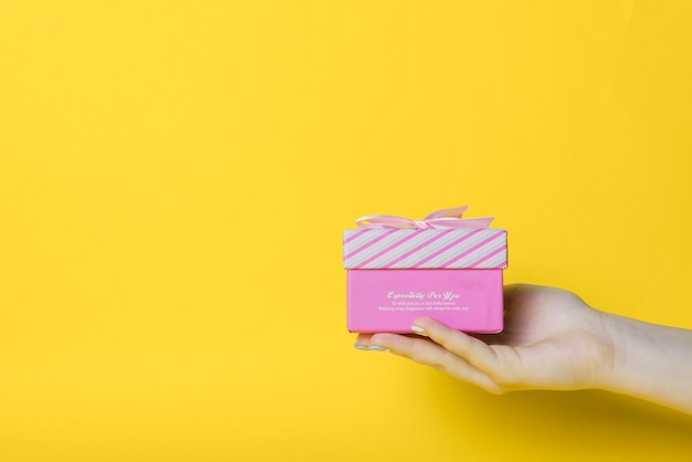 Close-up of hand holding pink box against yellow background