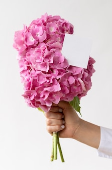 Крупным планом рука держит букет розовых гортензий