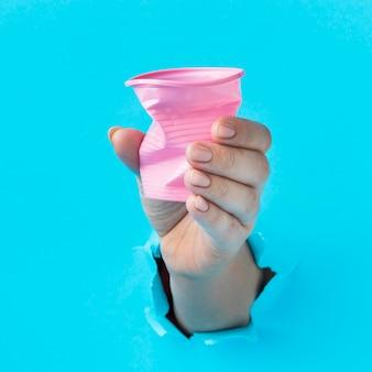 Mano del primo piano che tiene tazza di plastica