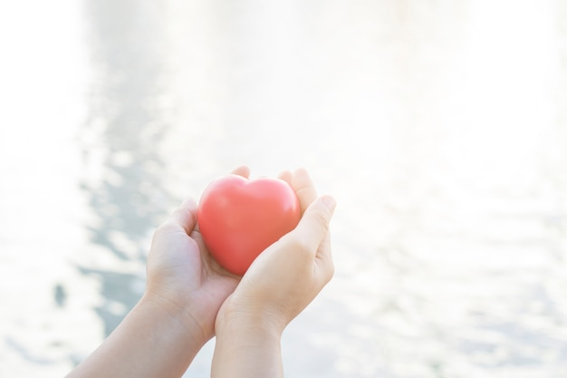 Close up hand holding red heart on soft river and water background