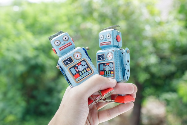 Close up on hand holding retro robot tin toy