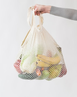 Close-up hand holding reusable bag with fruits and vegetables