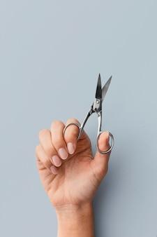 Forbici della holding della mano del primo piano