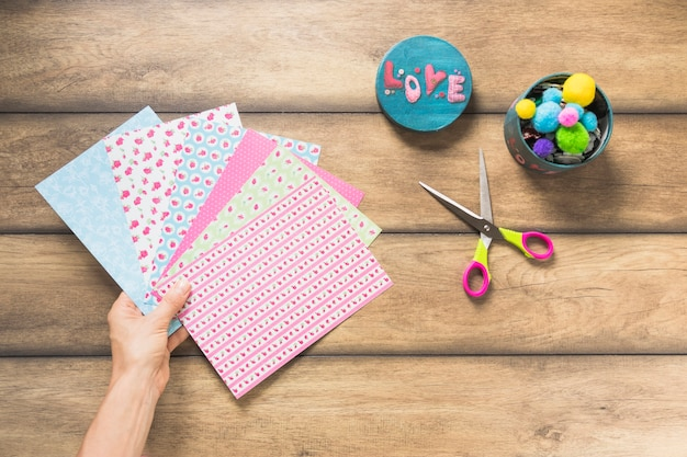Close-up of hand holding scrapbooking paper with container and scissor on wooden table