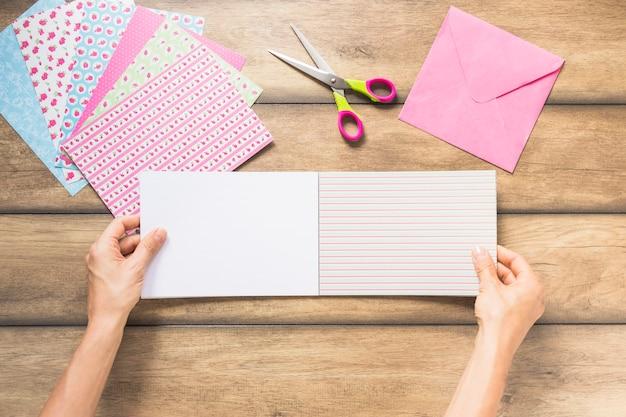 Primo piano della carta scrapbooking della tenuta della mano con le forbici sulla tavola