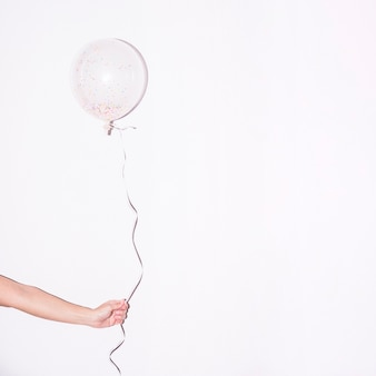Close-up of hand holding single white balloon with colorful sprinkle inside it against white backdrop