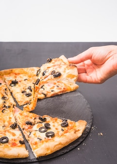 Close-up of hand holding slice of pizza on dark slate