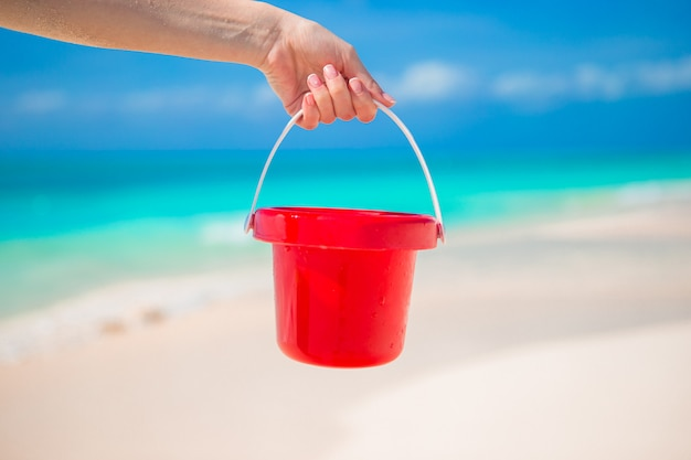 Close up hand holding a small red bucket on tropical beach