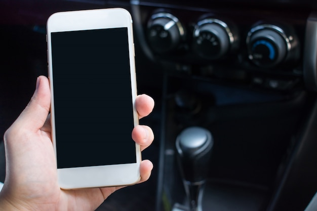 A close up of a hand holding a smartphone in the car for the trip. with copy space.