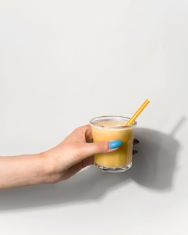 Close-up hand holding smoothie glass