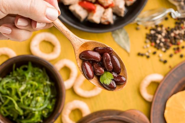 豆とスプーンを持っているクローズアップ 無料写真