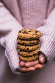 Close-up of hand holding stack of chocolate chips cookies