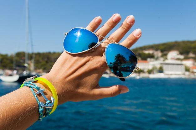 Крупным планом рука держит стильные солнцезащитные очки на открытом воздухе