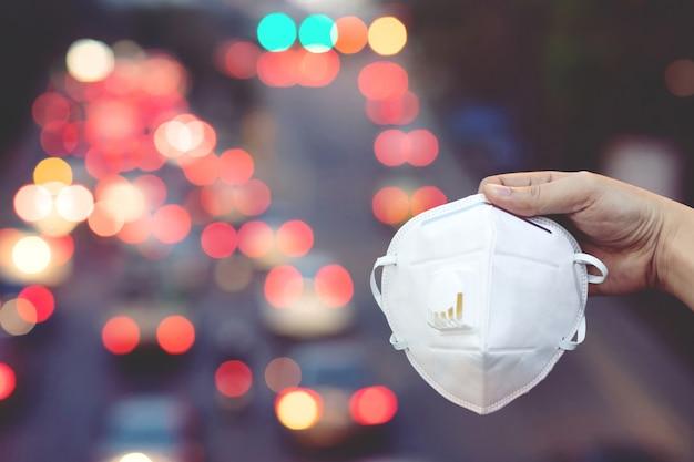 屋外で顔の衛生的なマスクの鼻を身に着けている提出物を持っている手を閉じます。エコロジー、大気汚染車、環境およびウイルス保護の概念健康効果の都市有毒なほこりに対するインフルエンザの健康