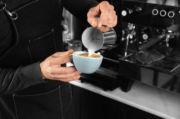 Крупным планом рука держит вкусную кофейную чашку