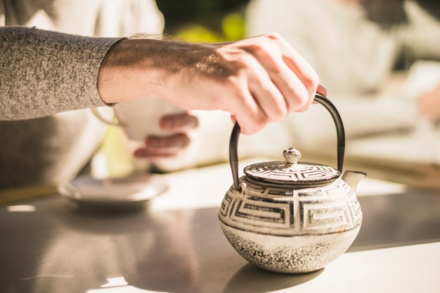 Close-up of hand holding traditional kettle on table