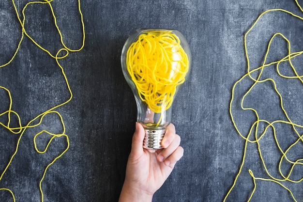 Close-up of hand holding transparent light bulb with yellow yarn on blackboard