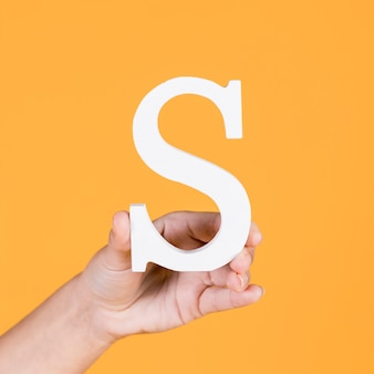Close-up of a hand holding up the alphabet s