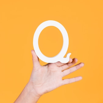 Close-up of a hand holding up the letter q