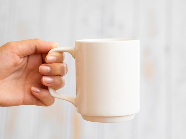 Close-up hand holding up a mug