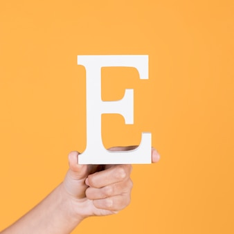 Close-up of hand holding up the uppercase capital letter e over yellow background