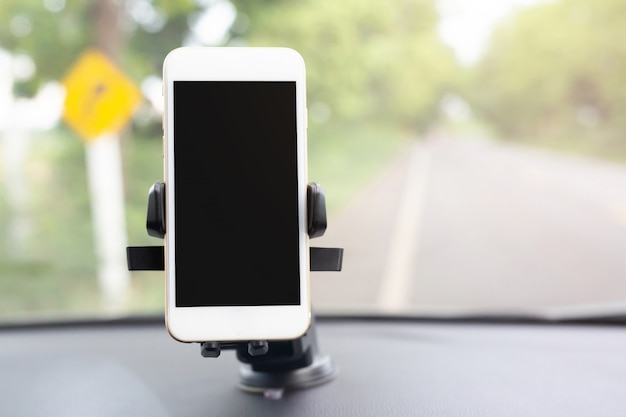 Close up hand holding using mobile smart phone with black screen in car console front windshield holder stick.