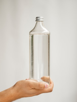 Close-up hand holding water bottle mock-up