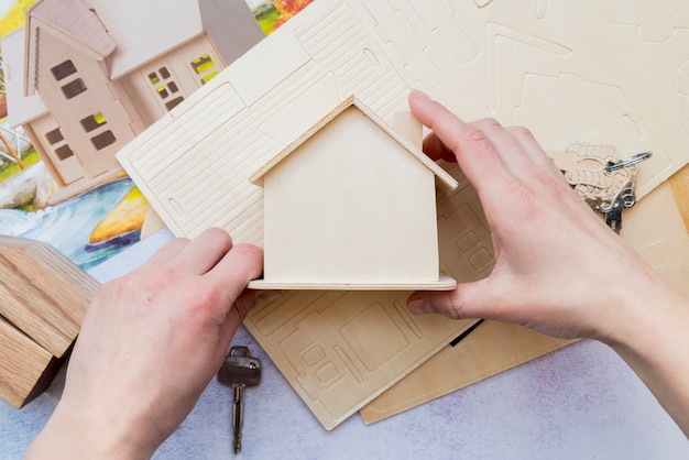 Close-up of hand holding wooden miniature house model