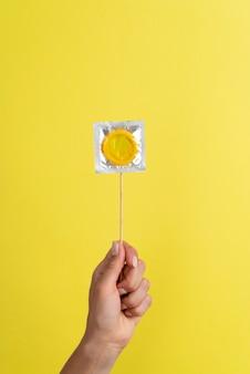 노란색 콘돔을 들고 손을 닫습니다
