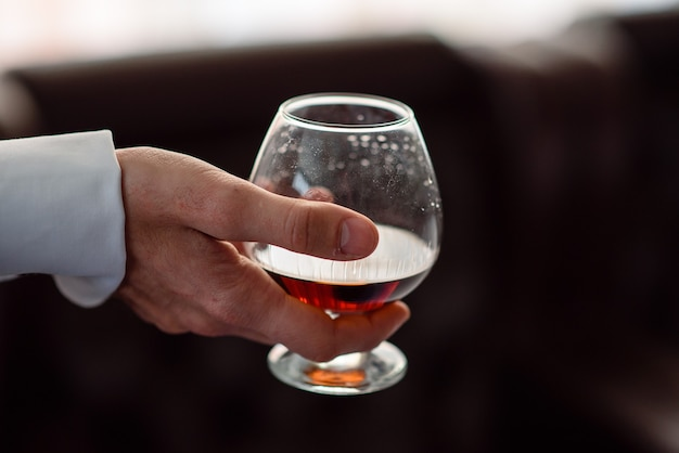 Close up on hand holds a glass of cognac