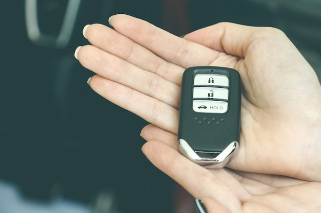 Close up hand holds modern remote control of car or car key on hand with retro background.