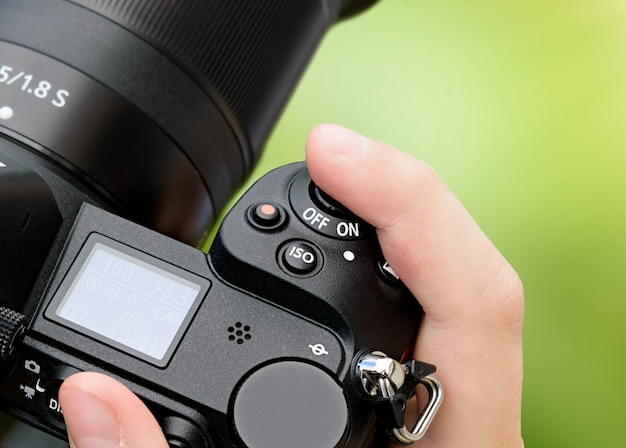 Close-up hand holds slr camera with finger pushing shutter button on green abstract background.