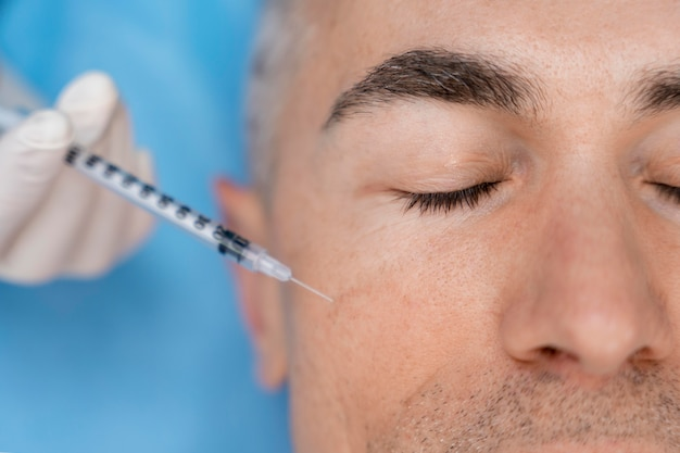 Close up hand injecting patient