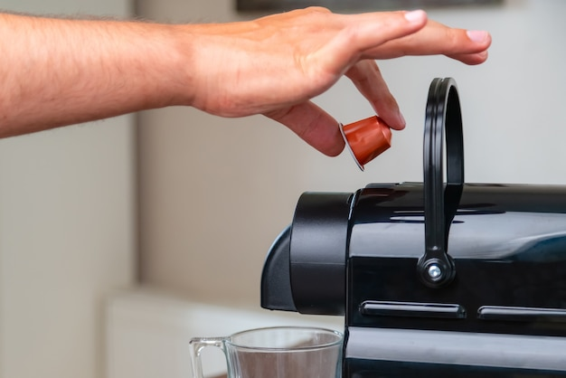 Close up of hand inserting a capsule into a coffee machine at home.