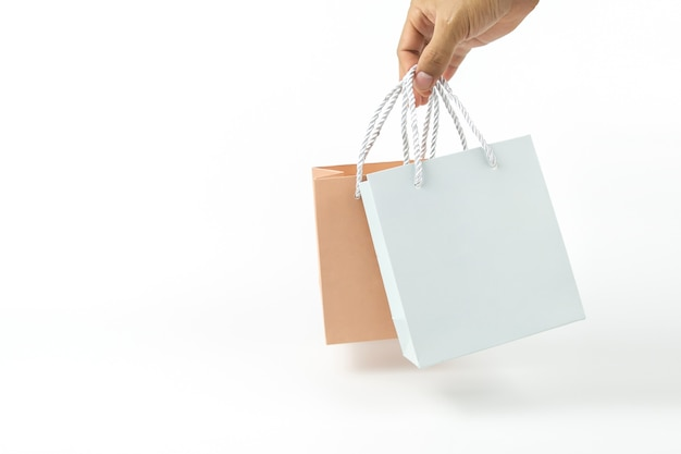 Close up hand is holding blank paper shopping bag on white