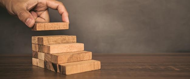 Рука крупным планом кладет башню из деревянных блоков, сложенную в ступеньку.