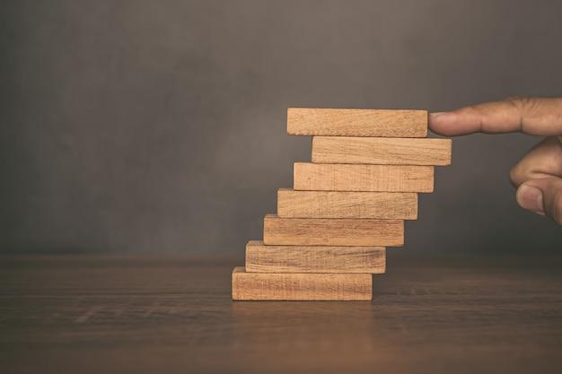 클로즈업 손으로 계단 단계에 쌓인 나무 블록 타워를 배치하고 있습니다.