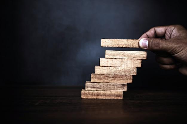 Крупным планом рука кладет башню из деревянных блоков, сложенную в ступеньку