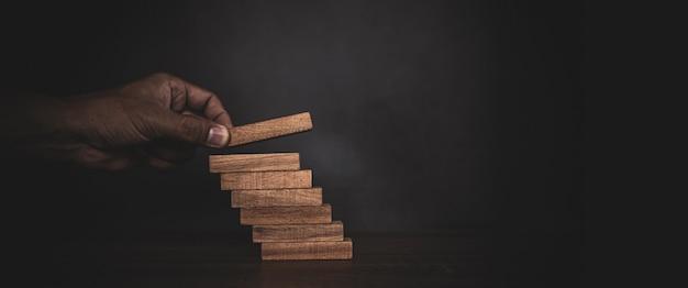 Рука крупным планом кладет башню из деревянных блоков, сложенную в ступеньку