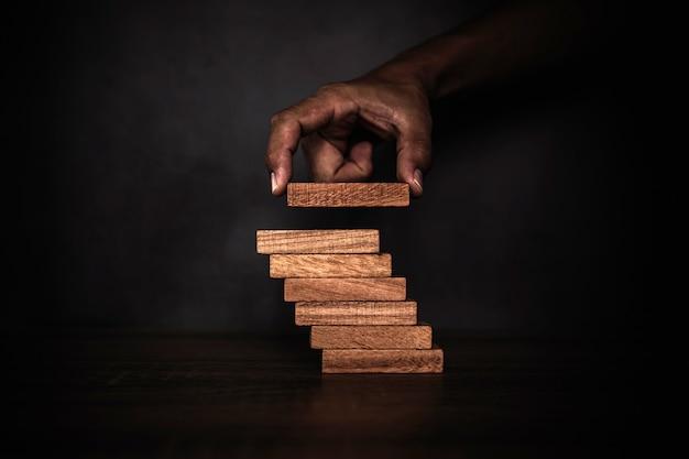 クローズアップの手は階段に積み上げられたウッドブロックタワーを配置しています