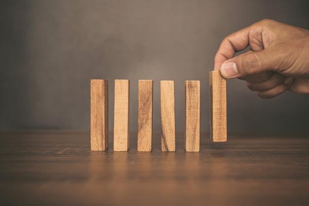 Крупным планом рука ставит башню из деревянных блоков с осторожностью, чтобы не допустить падения домино
