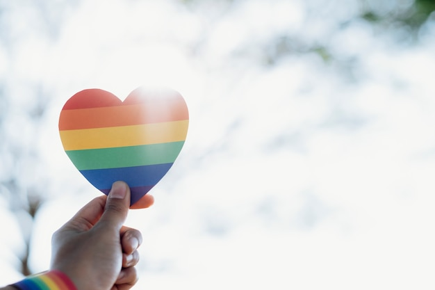 Close up hand of lgbtq couple holding rainbow heart.