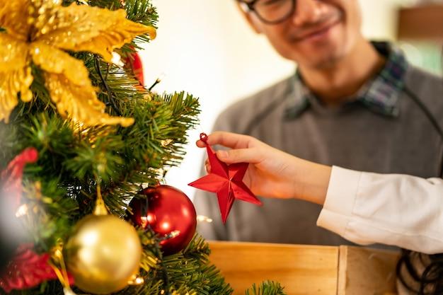 クリスマスツリーを飾る小さなアジアの女の子の手のクローズアップ